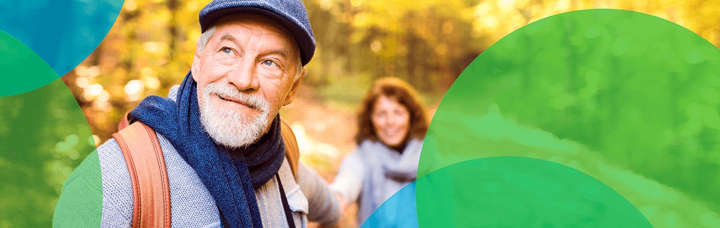 Older man in a scarf, hat and sweater holding the hand of a woman in a forest. Blue and green circles border them