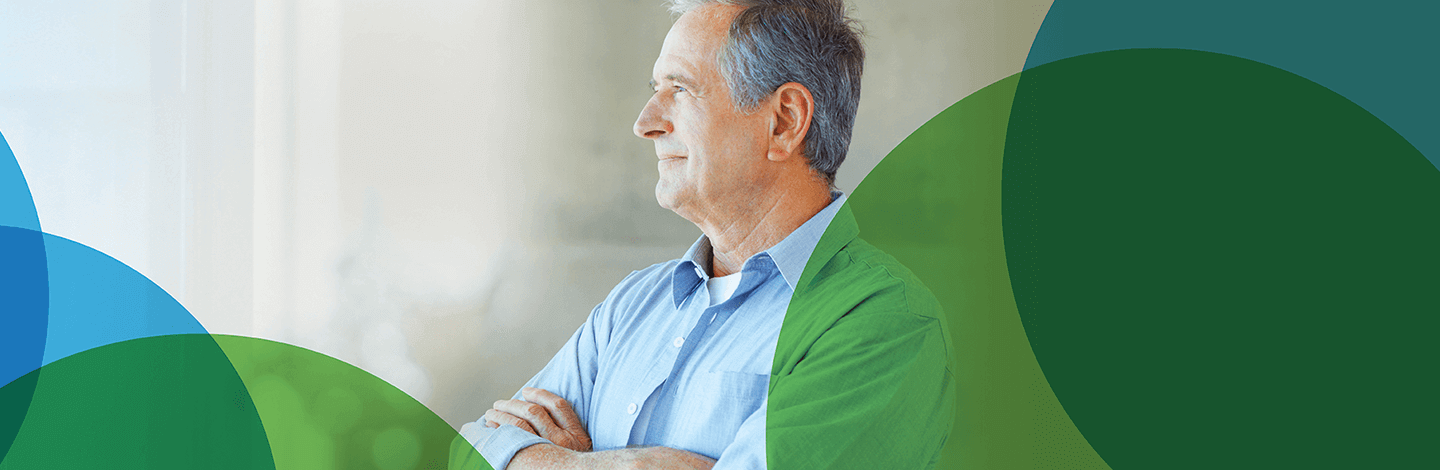 Image of an older man with crossed arms and blue shirt looking into the distance. Blue and green circles border him
